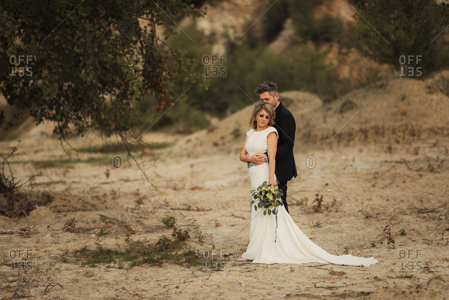 Bridal couple in embrace in remote setting