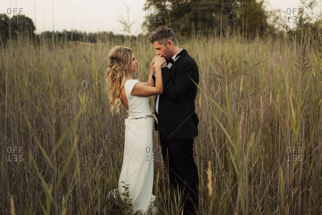 Groom kissing bride's hand in field