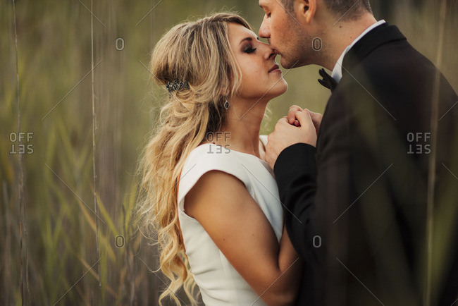 Groom kissing bride's forehead in field