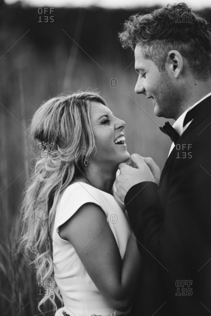 Laughing groom and bride in black and white