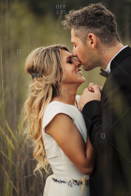 Groom kissing bride's nose in field