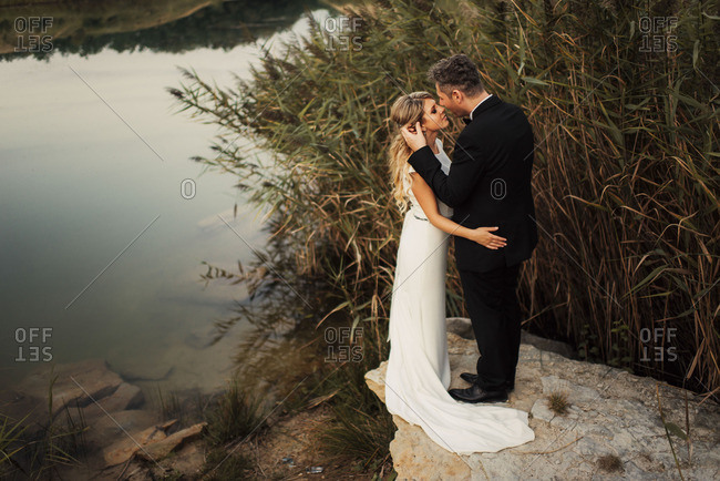 Bridal couple in tender embrace by pond