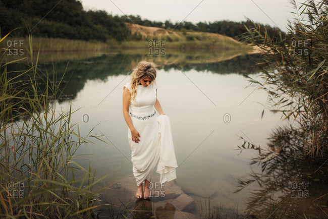 Barefoot bride on a pond's shore