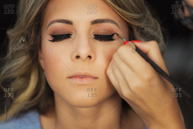 Applying eyeliner to bride's eyelid