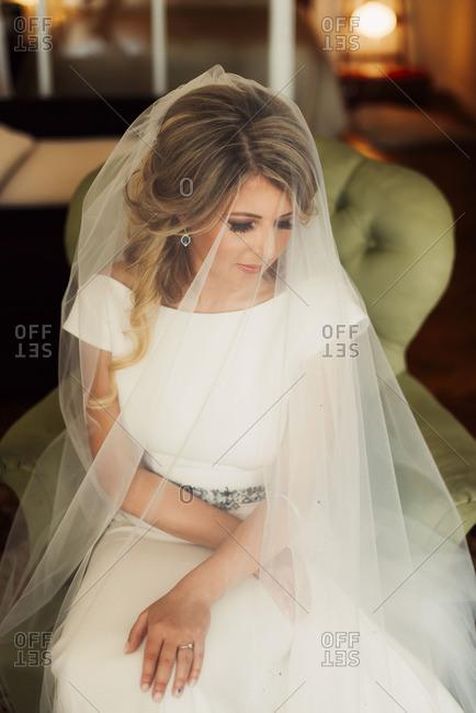 Bride in chair under a veil