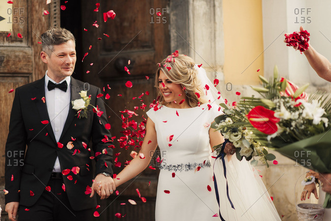 Smiling couple leaving church after wedding