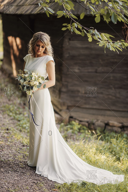 Bride in gown by rustic building