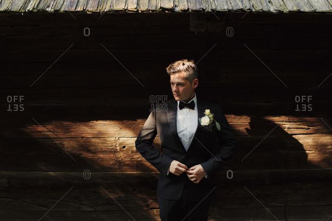 Groom in tux by rustic building