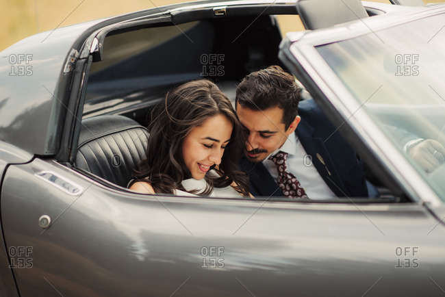Smiling bridal couple in sports car