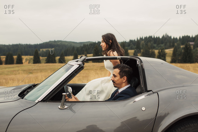 Bride and groom in a sports car