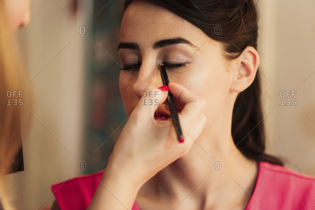 Woman having eyeliner applied