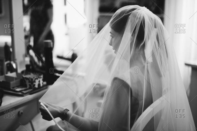 Bride in veil by vanity table