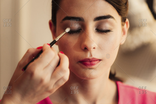 Woman having eye makeup put on