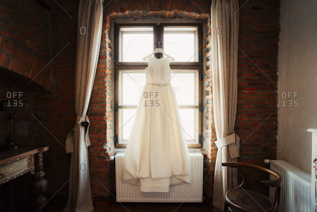 Bridal gown hanging in sunny wedding