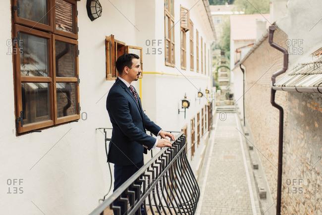 Groom standing on exterior balcony