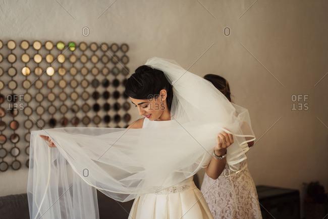 Bride in veil getting dressed