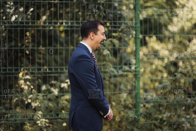 A laughing groom by fence