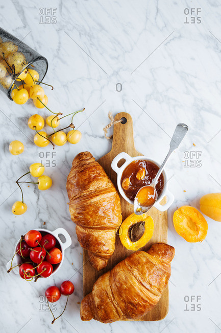 Croissants, apricots, variety of cherries and homemade apricot jam