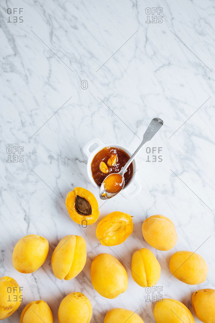 Apricots and a small jar of homemade apricot jam with seeds on a marble table