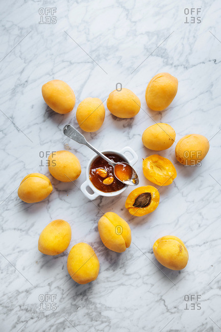 Apricots with a jar of homemade apricot jam with seeds on a marble table