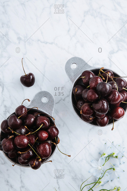 Black cherries in dishes on a marble counter