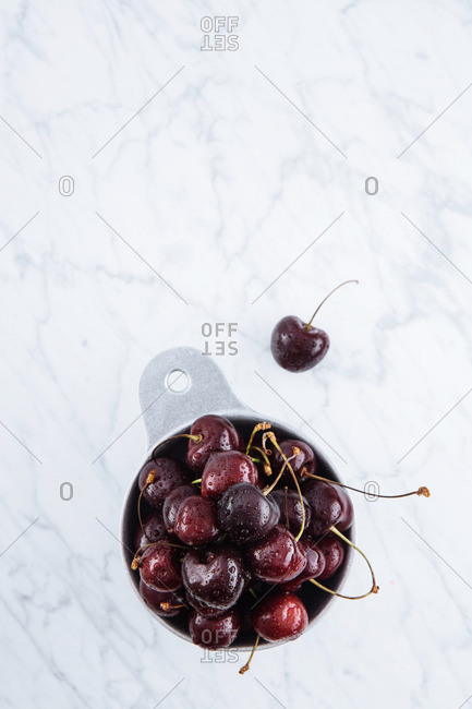 Top view of black cherries in dishes on a marble counter