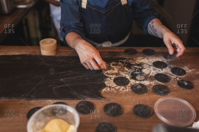 Chef making squid ink pasta coins in open kitchen