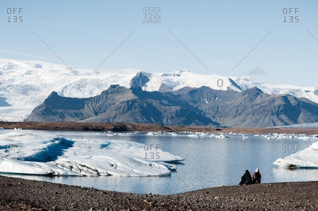 Picturesque view of tourists sitting on the stone shore and enjoying stunning glacier lagoon