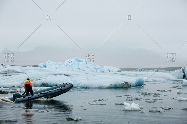 Scenic view of a man in colorful jacket crossing glacier lake in inflatable boat and passing by large and small ice chunks drifting on surface