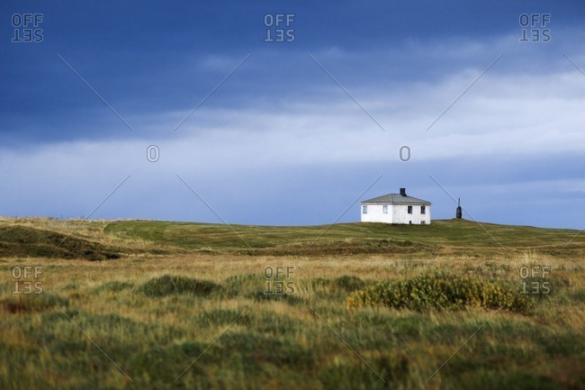 Evening scenery of remote humble country house standing in the middle of grassy field