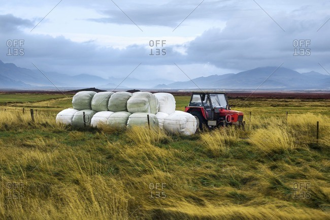 Rural landscape of small red lone tractor standing in field and hay bales in covers lying beside
