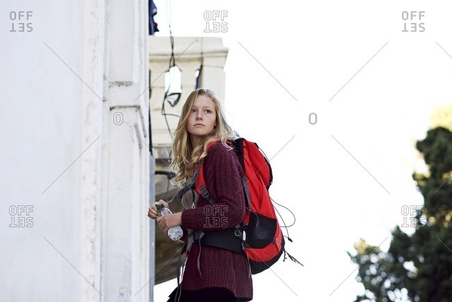 Young woman walking with water bottle and red backpack