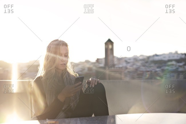 Blonde woman sitting and texting on her phone