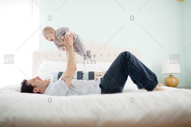 Father lying on a bed and holding baby in the air