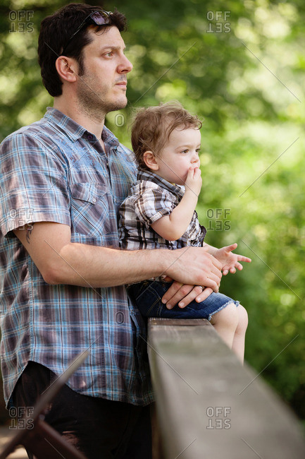 Portrait of father holding toddler and looking into the distance