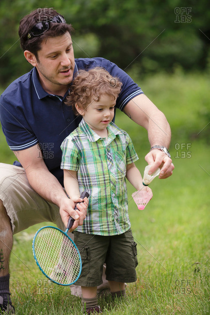Father teaching toddler to play badminton