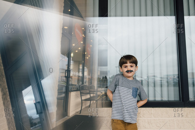 Little boy standing by window wearing pretend mustache