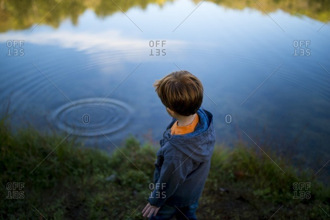 Little boy standing by a lake