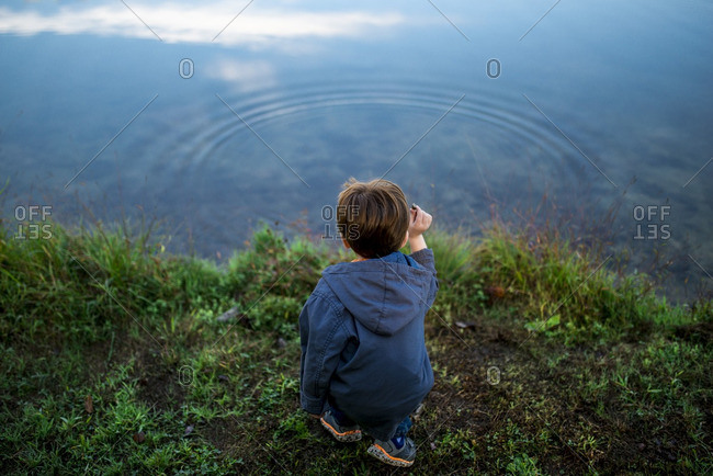 Little boy throwing stones into a lake