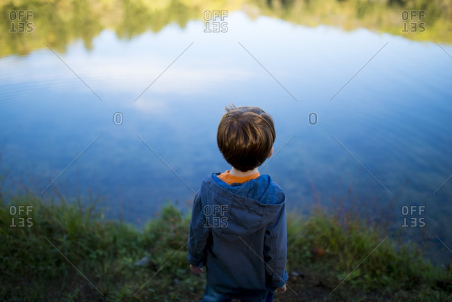 Little boy looking out at a lake