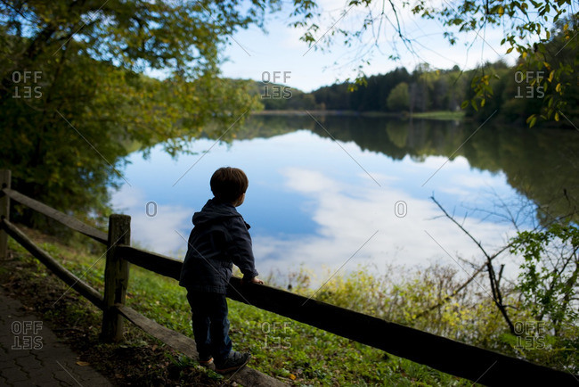 Little boy standing on fence looking out at a lake