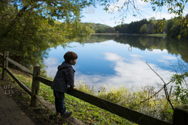 Side view of a little boy standing on fence looking at a lake