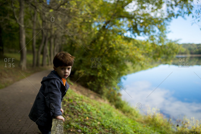 Little boy standing on fence by a lake