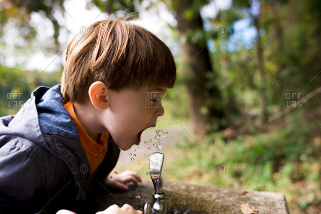 Little boy taking a drink from a water fountain