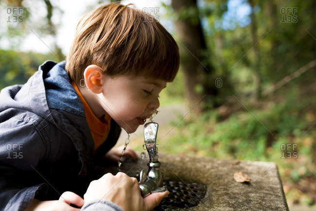Little boy taking a sip from a water fountain
