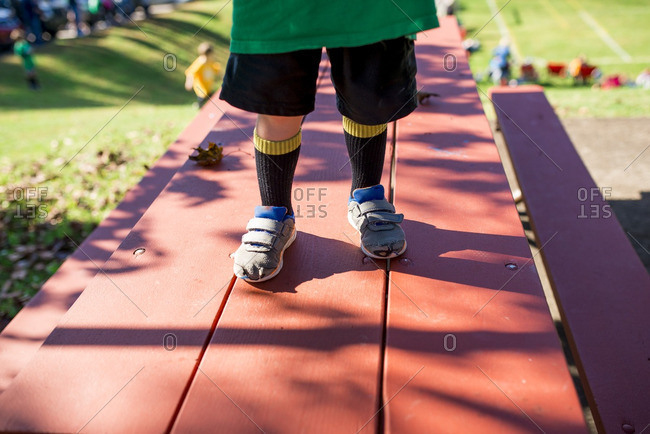 Little boy standing on top of a picnic table