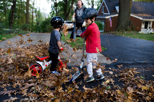 Boys riding bikes and scooters in a pile of leaves