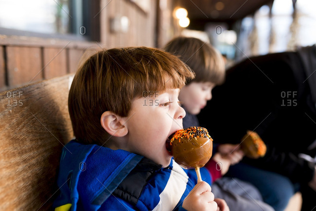 Little boys eating caramel apples with sprinkles