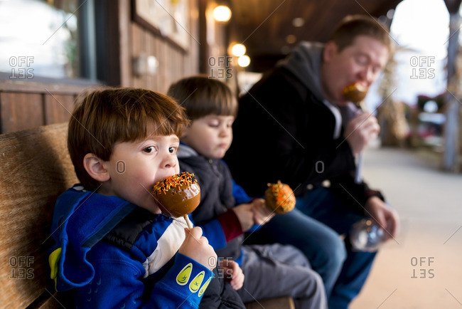 Little boys and their dad eating caramel apples with sprinkles