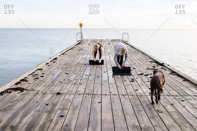 Two women rolling up yoga mats on a pier